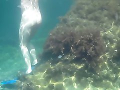 Nudists in the Crimea. Girl underwater in flippers.
